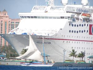 Bahamian sloop against a giant cruise ship in Nassau